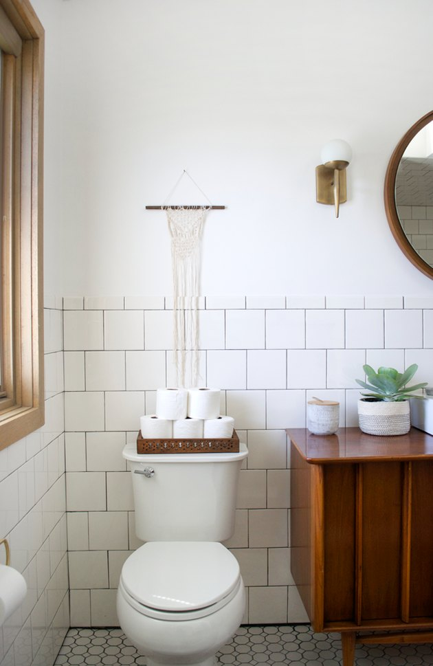 guest bathroom idea with toilet paper stacked in a try on the back of a toilet in a white-tiled bathroom