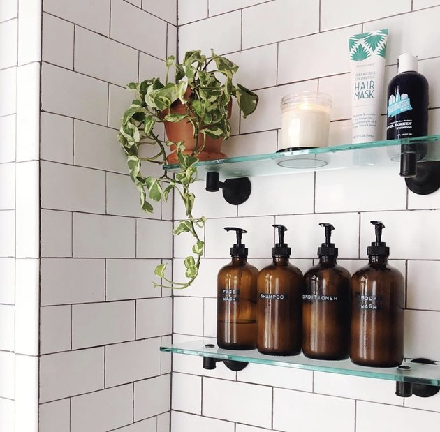 guest bathroom idea with four amber bottles with labels on a glass shelf in a white tiled shower