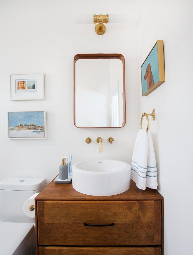 guest bathroom idea with a white bowl sink on top of a wooden vanity in a white guest bathroom