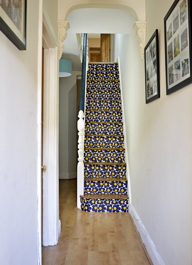 white staircase with marimekko stairs wallpaper on risers and wood treads