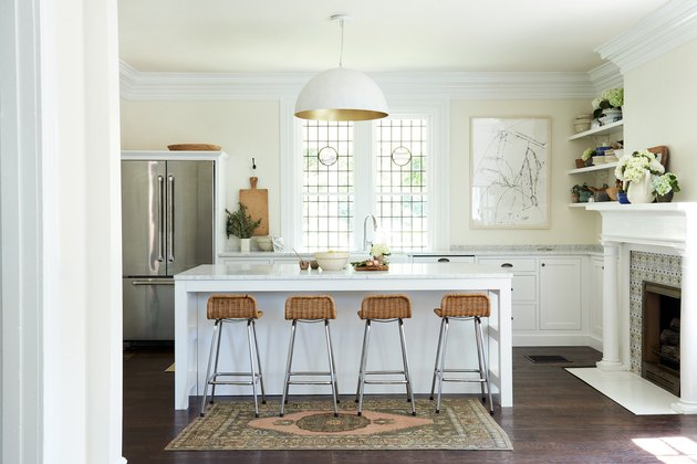 White kitchen design with dome shaped pendant and bar seating