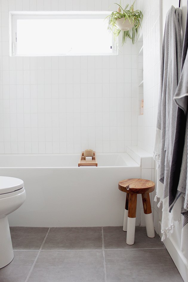 guest bathroom idea with a small rustic wooden stool with white-dipped legs next to a white bathtub