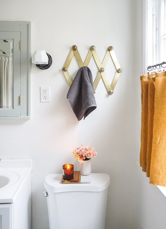guest bathroom idea with a brass accordion peg rack hung over a toilet in a small white bathroom