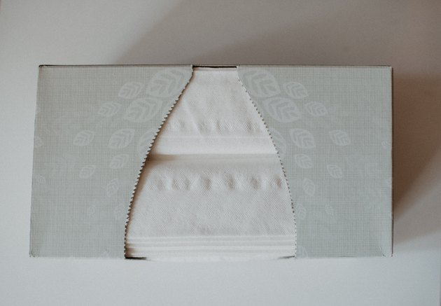 grey rectangular Kleenex tissue box covered in leaf print