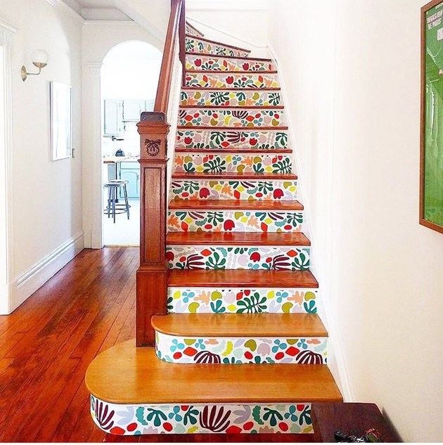 matisse stairs wallpaper on risers of wooden staircase in a white entryway