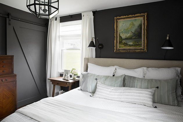 Vintage-inspired dark gray bedroom idea with upholstered headboard and sliding barn door
