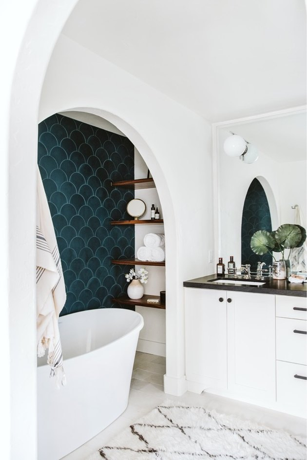 white bathroom with teal color scallop wall tile with freestanding tub