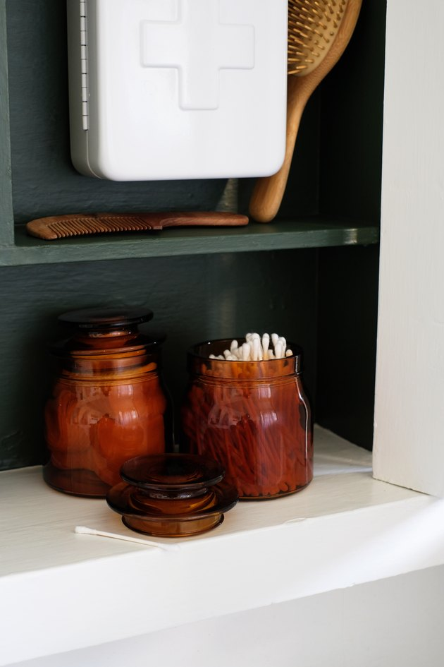recessed medicine cabinet with painted green wood interior, glass jars of cotton balls, q-tips, white first aid kit, wooden brushes