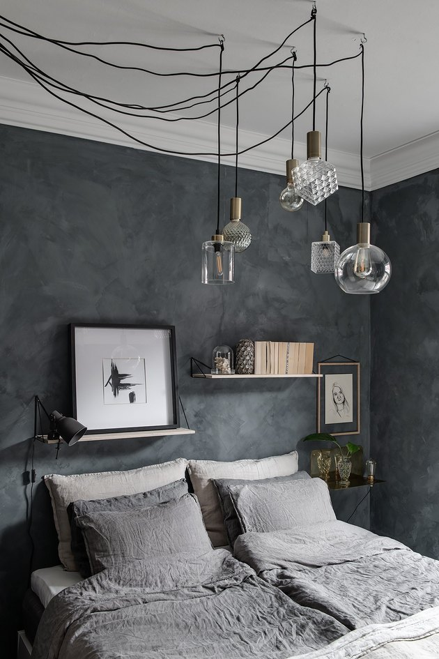 Dark gray bedroom idea with suspension lighting and open shelving