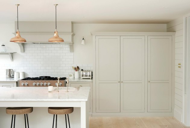 White kitchen design with copper pendant lights