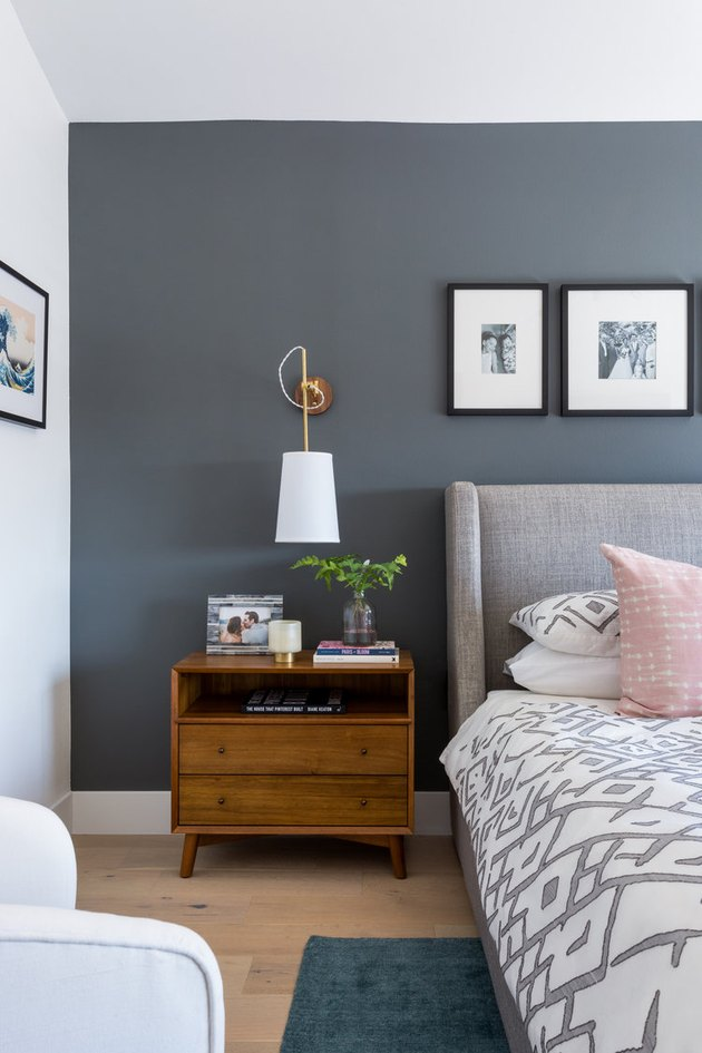Eclectic gray bedroom idea with upholstered headboard and wood nightstand