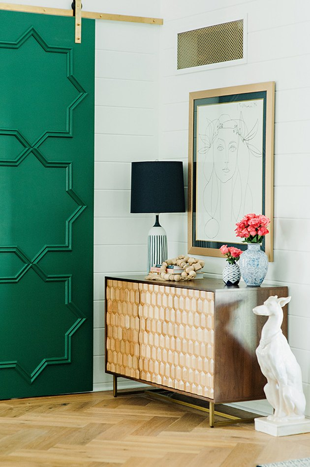 Traditional entryway table with green door and decorative accents
