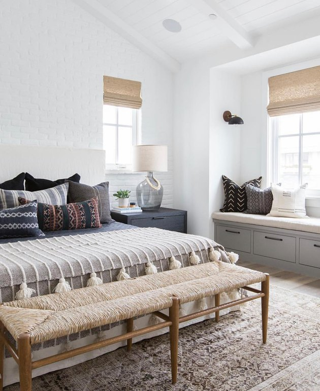 Modern gray bedroom idea with layers of textiles and an accent bench