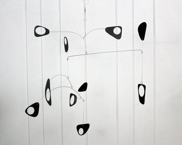 Modern minimal mobile with abstract black pieces on thin wire