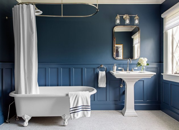 blue apartment bathroom idea with wainscoting and clawfoot tub with pedestal sink