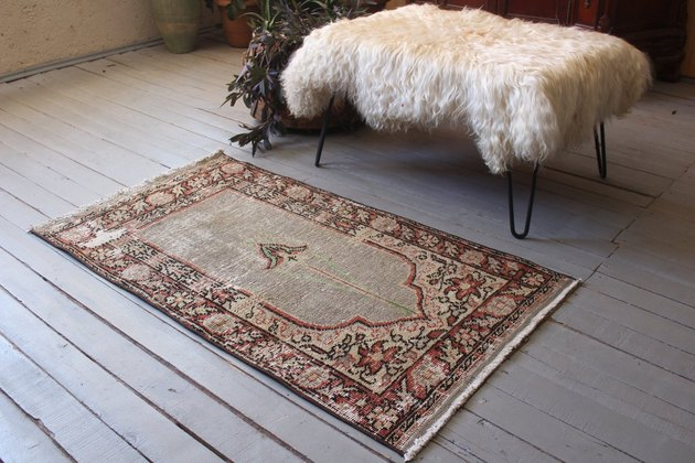 Prayer rug in front of bench with sheepskin throw