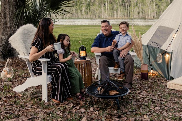 Family of four sitting in Adirondack chairs around the fire pit