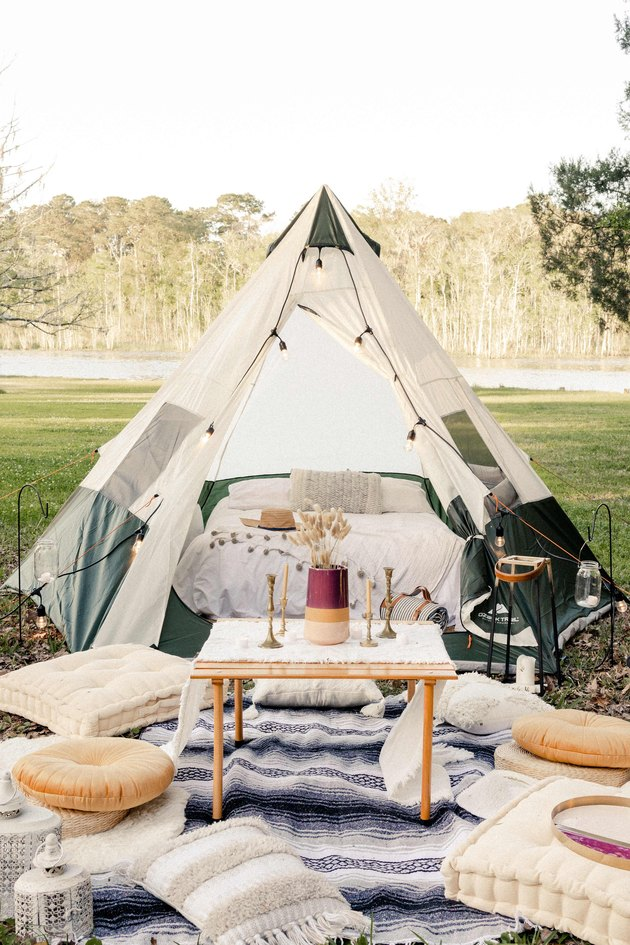 Glamping tent with table, poufs, pillows and blankets