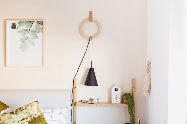 Scandi-style black pendant lamp hanging on wall in bedroom.