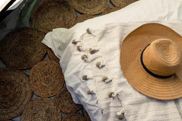 Braided jute rug, pom pom blanket and straw hat inside tent