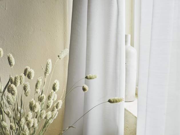 light gray curtains near dried plants and a white vase