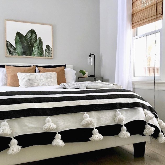 masculine boho bedroom with striped throw and plant artwork