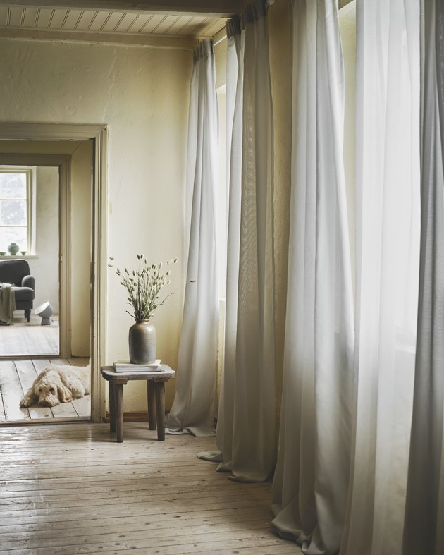 room with light gray curtains and side table and dog in backgroun