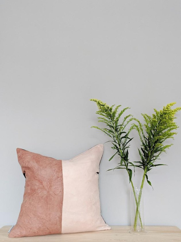 two-toned pillow with greenery nearby