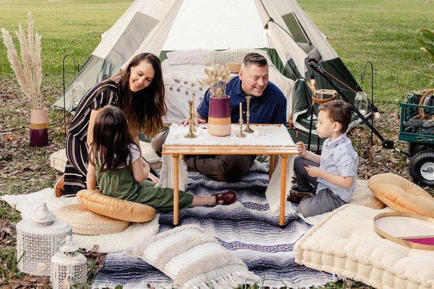 Family of four lounging around table in glamping site