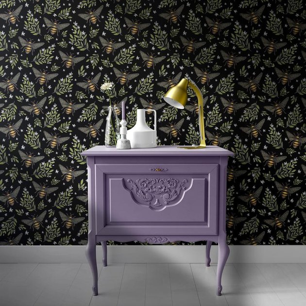 purple cabinet with bee pattern wallpaper wall behind it