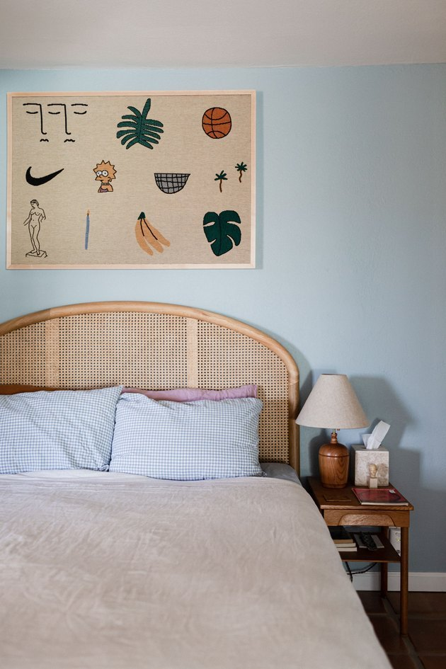 blue and beige desert house color palette in bedroom with rattan bedframe and wall hanging