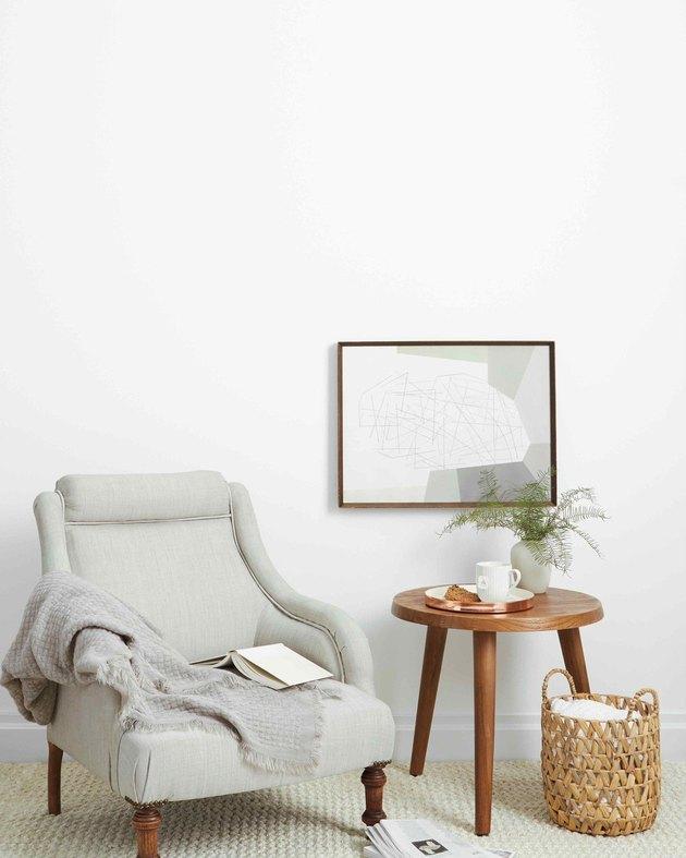 sofa chair near wood table and framed artwork