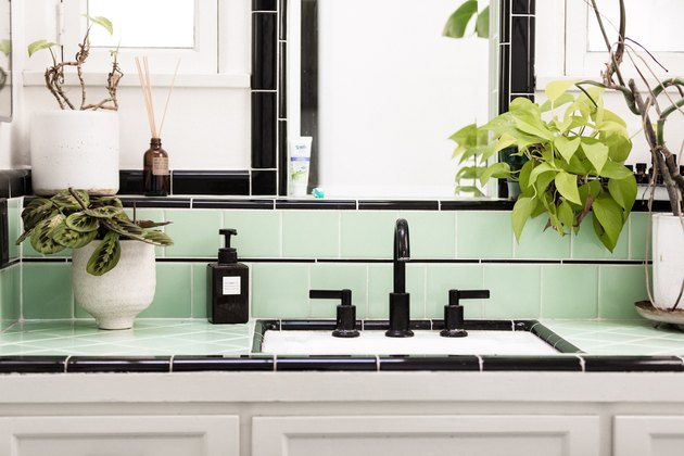 bathroom vanity with white cabinets, green and black ceramic tile, white planters with greenery