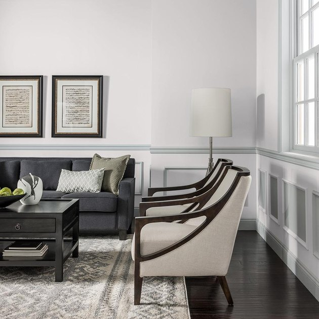 living room area with two chairs and a black couch
