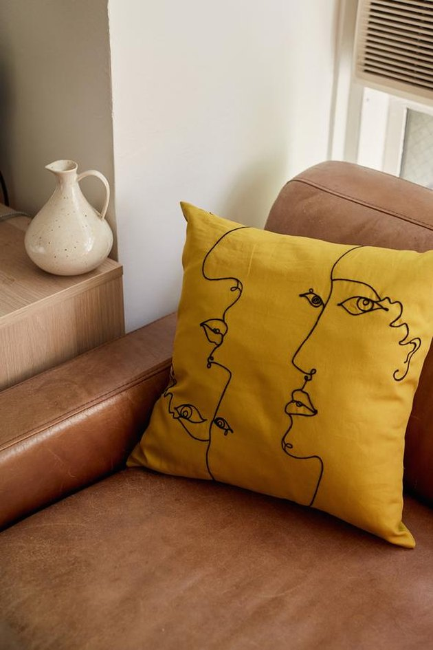 yellow pillow with face drawing on chair