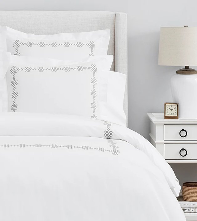 bed with white sheets and white night stand