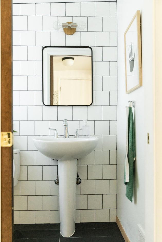 bathroom, large white subway tile wall, white pedestal sink with silver faucet, rectangular mirror with black trim, green hanging towel