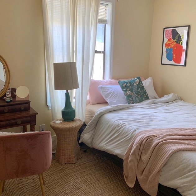 bedroom with pink and white bed and framed artwork