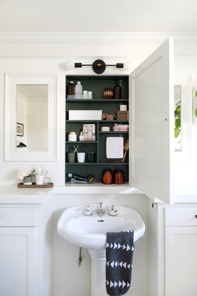 white pedestal sink, recessed medicine cabinet with green interior paint, white bathroom vanities, mirrors with white wood trim