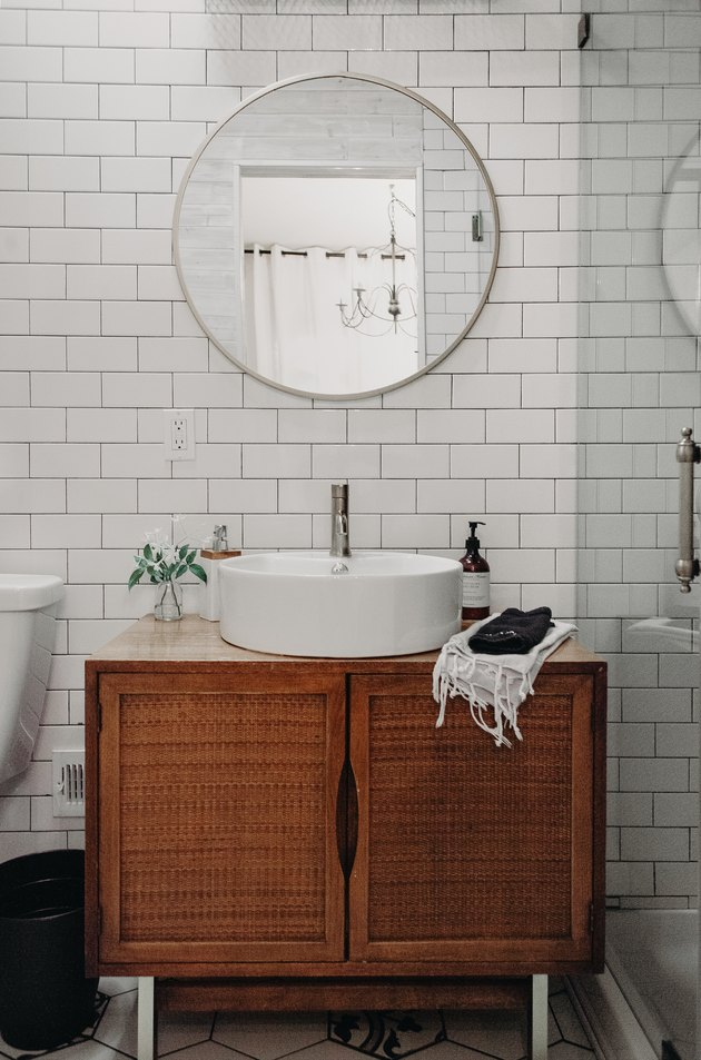 wood vanity with white vessel sink, round mirror with silver trim, white subway tile wall, glass shower door