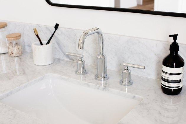 quartz bathroom countertop, silver faucet, white undermount sink, black hand soap dispenser, white toothbrush holder