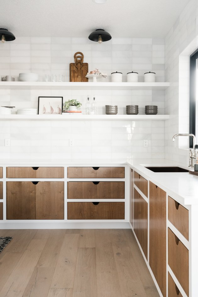 Kitchen lighting idea with open shelving and wood cabinets paired with white subway tile