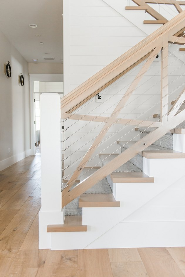 X-shaped farmhouse stair railing with cables and light wood