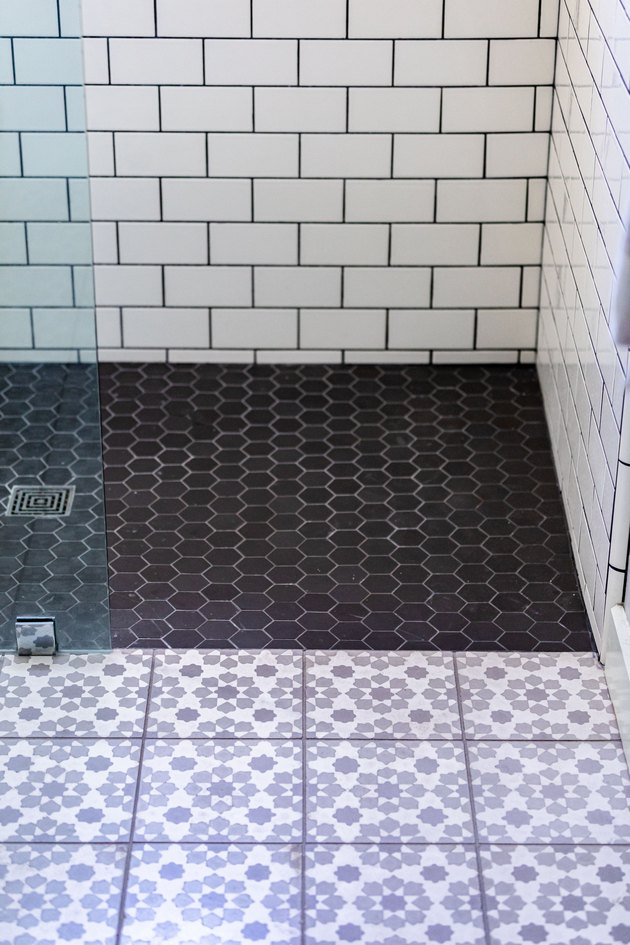glass shower door, white subway tile wall with black grout, black hexagon tile floor in shower, purple and white floral design on square floor tiles