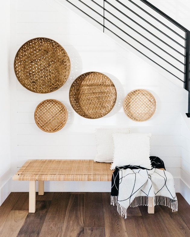 Black linear farmhouse stair railing with baskets hung on wall