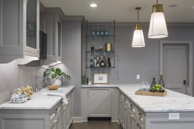 light gray basement kitchen with gold lights and glass shelves