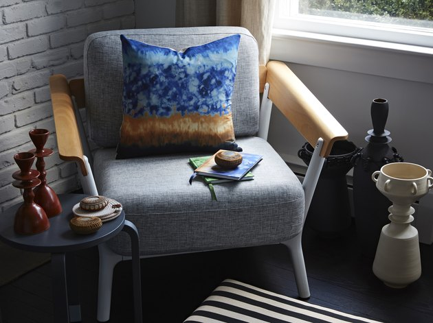 gray chair with blue pillow and decorative objects nearby