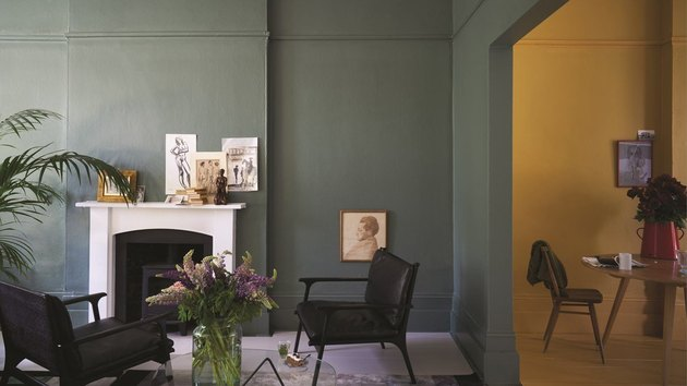 living room with dark green walls and white fireplace