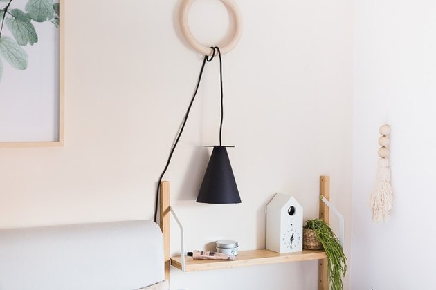 shelf with black hanging lamp and wall hanging nearby