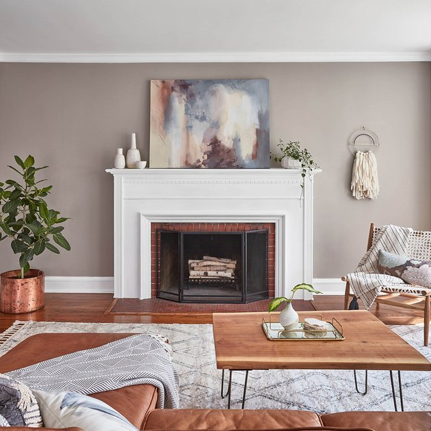 living room with beige wall and white fireplace